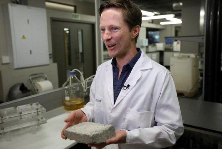 El doctor Dyllon Randall sostiene un ladrillo hecho con orina en un laboratorio de la Universidad de Ciudad del Cabo.