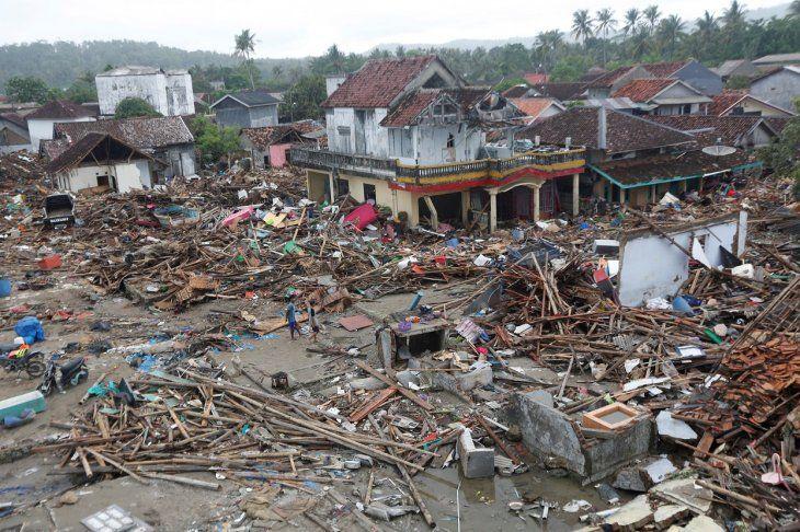 Los residentes locales caminan entre los escombros en un área devastada  después de que un tsunami golpeó el Estrecho de Sunda en Sumur