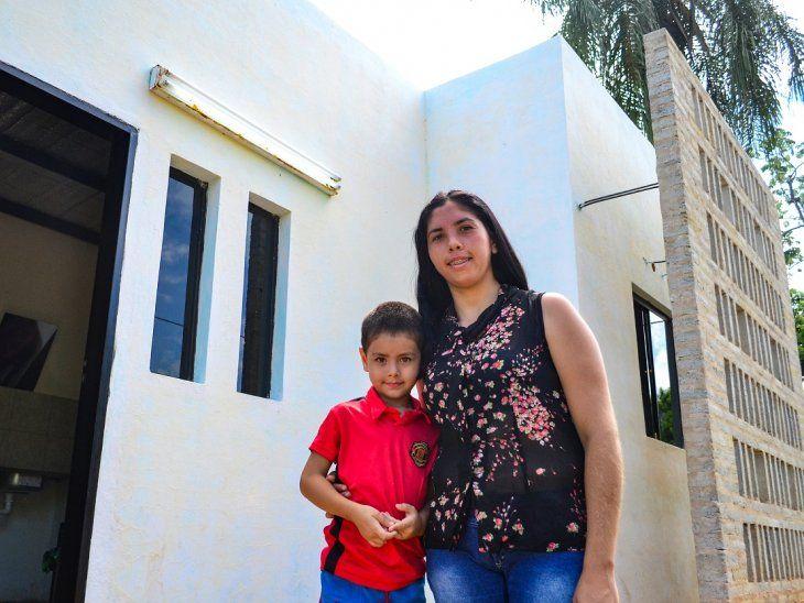 Carolina Espínola y su hijo posan frente a su vivienda, situada en el asentamiento Don Antonio.