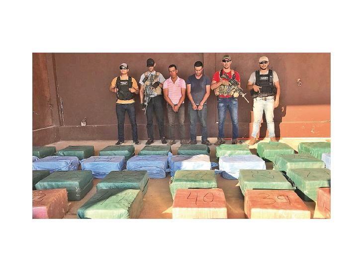 Detenidos. Los  detenidos junto a las bolsas con los panes de cocaína tras la verificación.