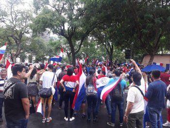 La mayoría de los manifestantes portan banderas paraguayas o los colores de la misma.