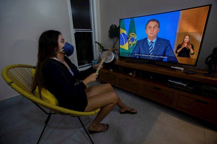 Una mujer con una máscara protesta golpeando una olla durante una declaración televisada del presidente de Brasil