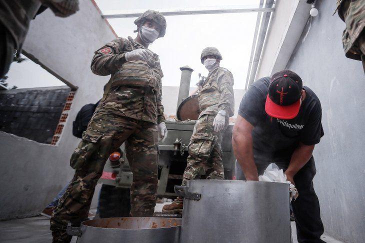 Habitantes esperan las ayudas distribuidas por soldados del Ejército en barrios pobres del Gran Buenos Aires