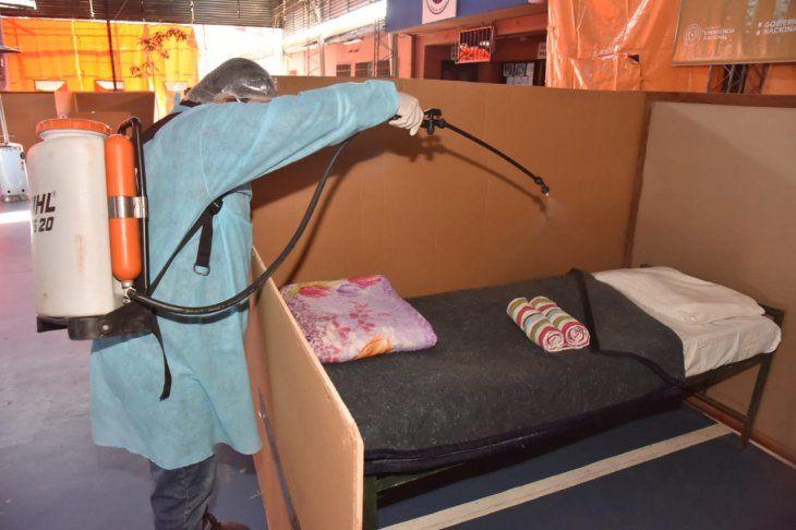 Un funcionario desinfecta una de las camas habilitadas en uno de los albergues habilitados por la Secretaría de Emergencia Nacional ante el frente frío que ingresó al país