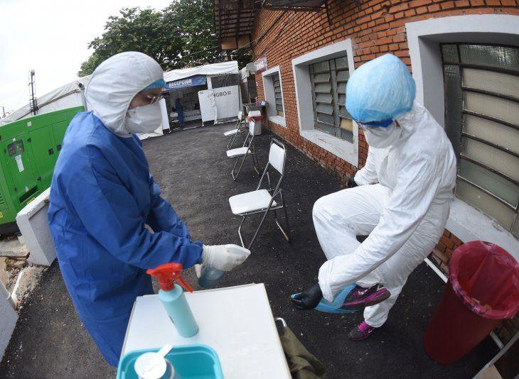 Dos profesionales de blanco a cargo de la toma de muestras para pruebas de Covid-19 en el Hospital de Barrio Obrero.