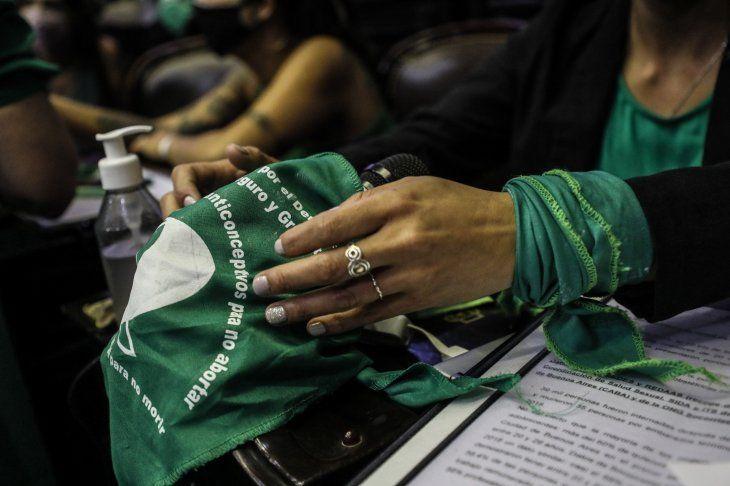 Fotografía que muestra a diputados que colocan en sus bancas  diferentes consignas a favor y en contra de la legalización del aborto.