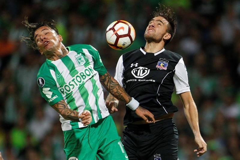 Dayro Moreno (i) deAtléticoNacionaldisputa un balón con Matías Zaldivia (d). Foto: EFE