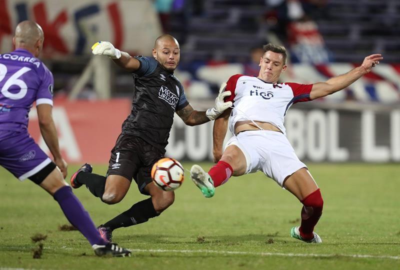 Rodríguez (c) de Defensor Sporting disputa un balón con Diego Churín (d) de Cerro Porteño. Foto: EFE
