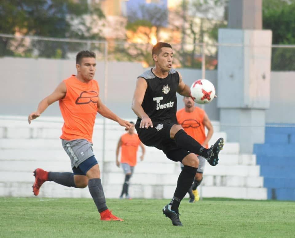 Parejo. Édgar Zaracho (der.) busca el dominio del balón ante la marca de Edgardo Orzusa.