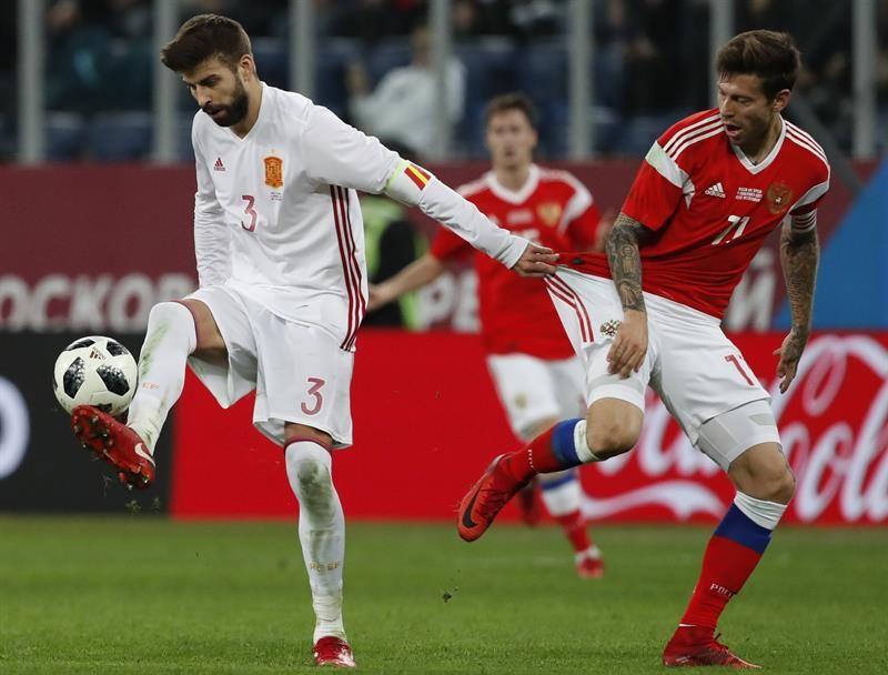 Fyodor Smolov (d) disputa un balón frente al jugador español Gerard Pique (i). Foto: EFE
