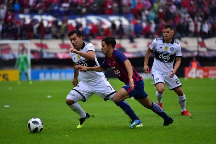 Jugadores de Olimpia y Cerro pelean por una pelota en un clásico del 2018.