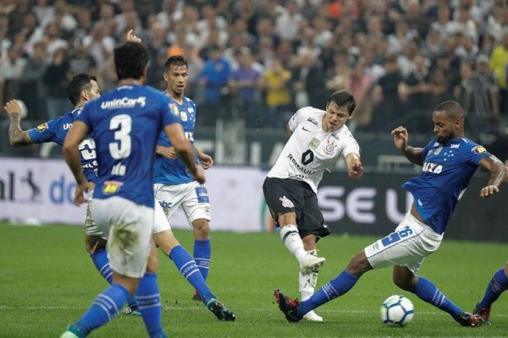 Romero (i) deCorinthiansdisputa el balón con Dede (d) de Cruzeiro.