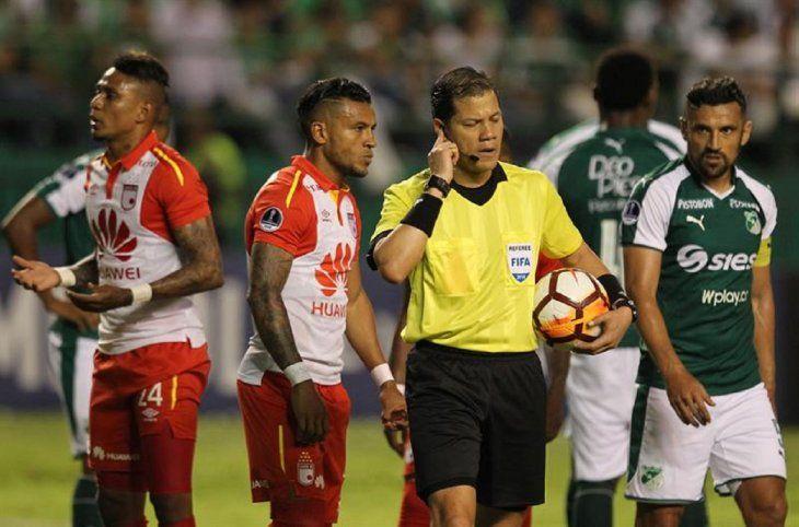 El árbitro peruano Víctor Carrillo (2-d) recibe indicaciones a través de un intercomunicador.
