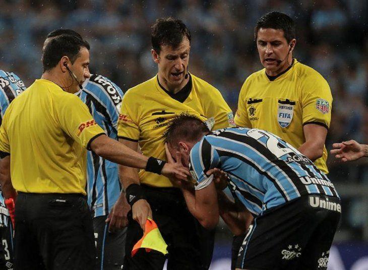 Bressan (2d) deGremiodiscute con el árbitro del encuentro Andrés Cunha (c).