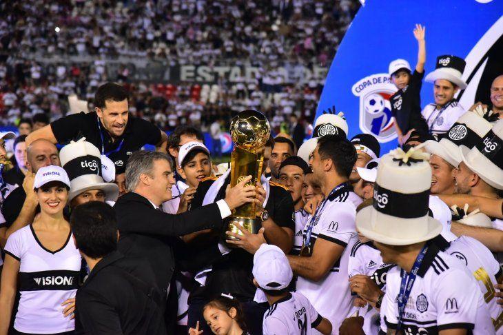 Javier Díaz de Vivar entregando la copa de campeón a Roque Santa Cruz.