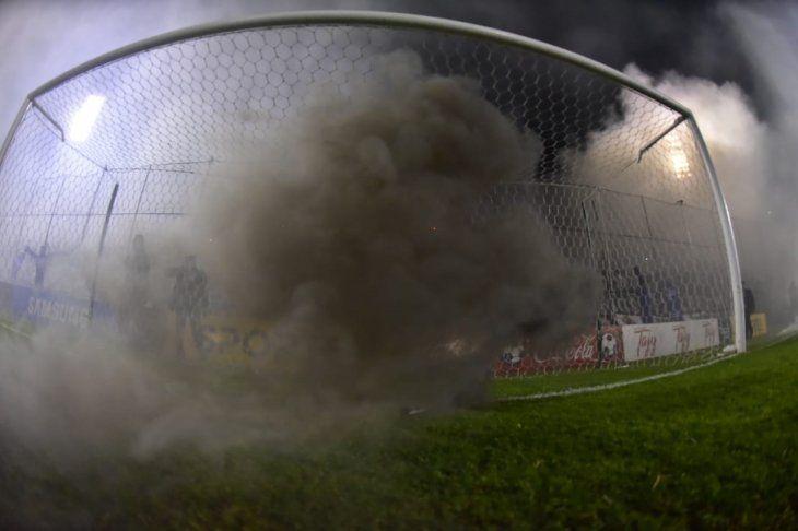 Hinchas arrojaron bengalas de humo.