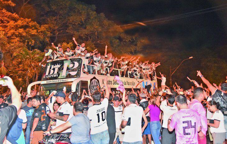 Los hinchas del Olimpia saludan a los jugadores mientras el bus va cruzando la avenida Mariscal López con destino al club ya cerca de la medianoche del miércoles
