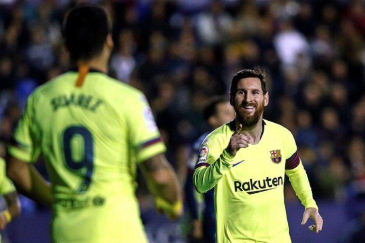 Messi se saluda con Luis Suárez.