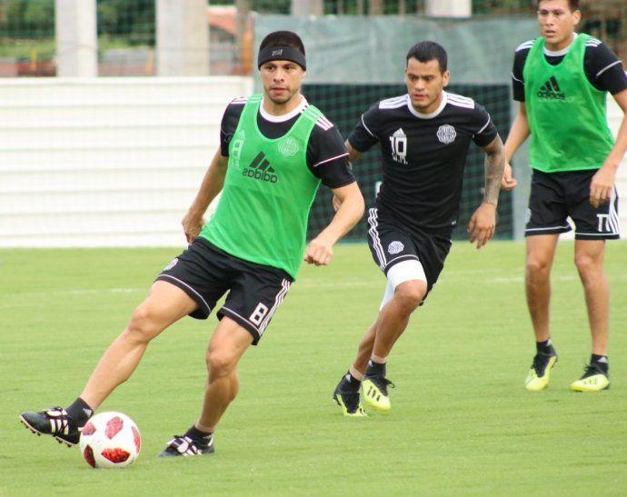 Rodrigo Rojas dirige el balón perseguido por William Mendieta.