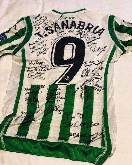 Antonio Sanabria recibe la camiseta firmada por sus ex compañeros del Betis.