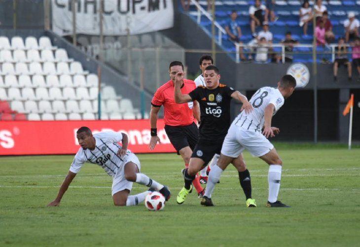 Jugadores de Libertad y Olimpia en acción durante el clásico blanco y negro.