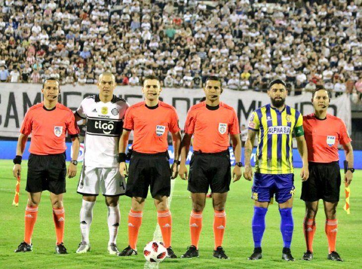 Rodrigo Burgos con el capitán de Olimpia y los árbitros.