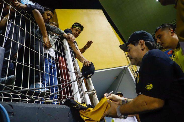 Diego Maradona firmando autógrafos.