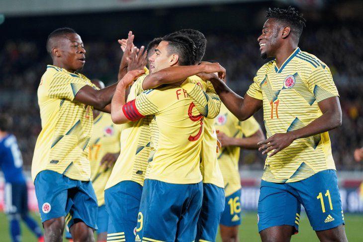Radamel Falco recibe el abrazo de sus compañeros tras su gol de penal ante Japón.