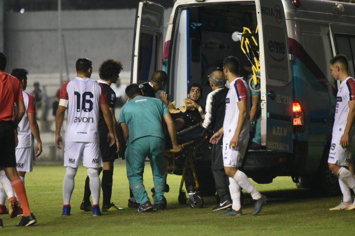 Ayrton Cougo siendo retirado en ambulancia tras el fuerte golpe que recibió en la cabeza.