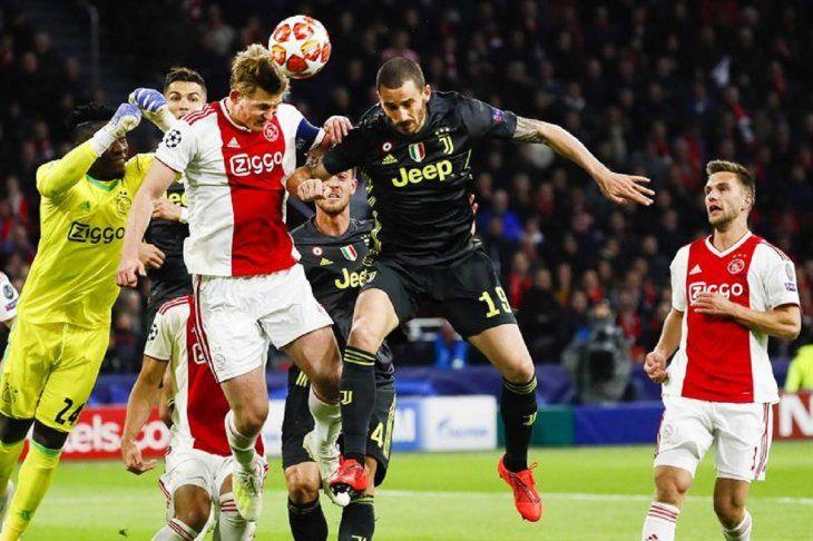 Jugadores de Ajax y Juventus pelean un balón aéreo.