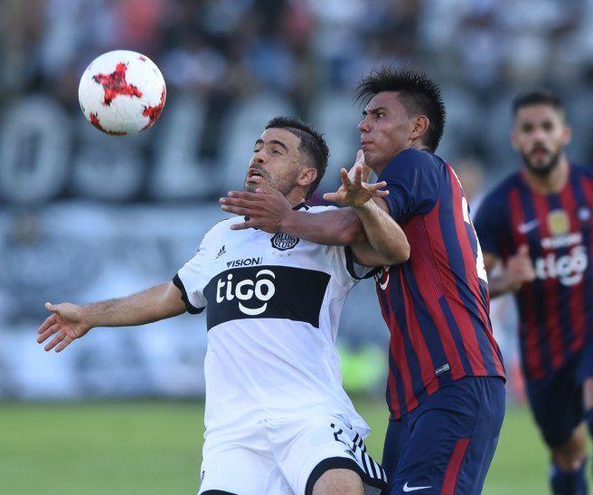 Santiago Arzamendia y Julián Benítez disputan el balón.