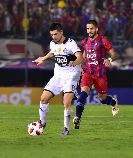 Visión de juego. Rodrigo Rojas realiza un pase largo ante la presión de Juan Aguilar. El volante se volvió un jugador determinante en el medio sector para recuperar y crear juego.