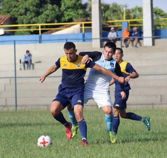 Un jugador de Trinidense soporta la marca de un futbolista de Atyreña.