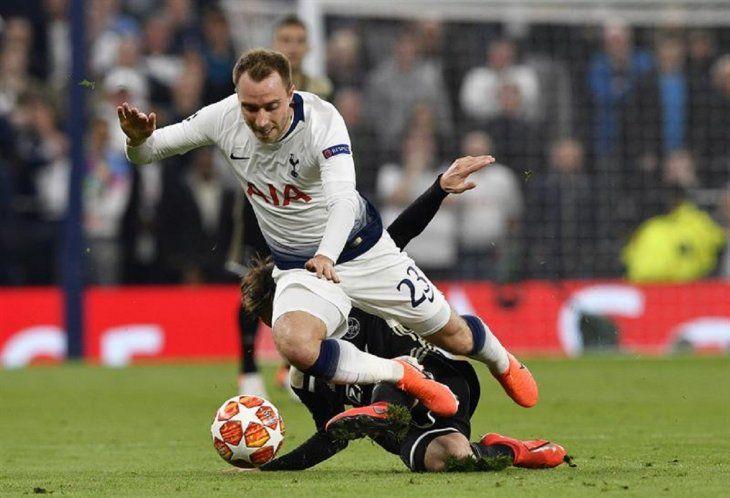 Eriksen(arriba) del Tottenham disputa un balón ante Nicolas Tagliafico.