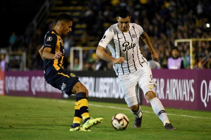 Gonzalo Bettini (i) de Rosario disputa el balón con Oscar Cardozo (d) deLibertad.