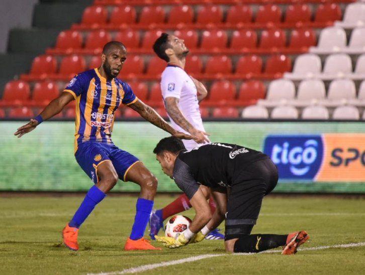 El portero Marino Arzamendia agarra la pelota ante la cobertura de Paulo Lima.