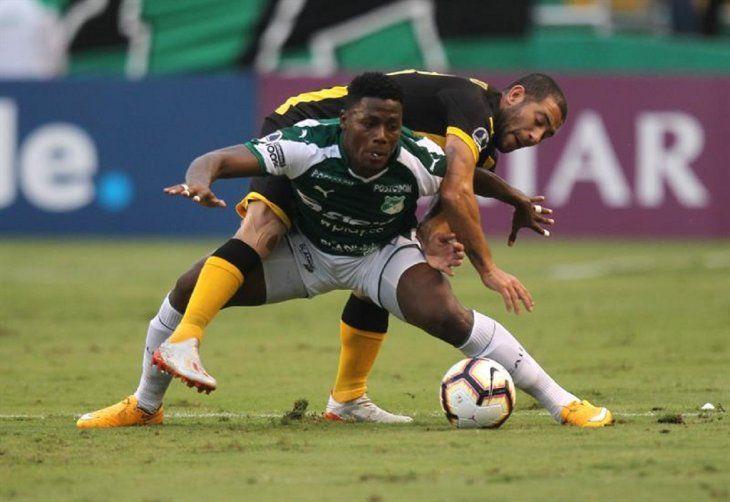 Dany Rosero (frente) de Deportivo Cali disputa un balón con Walter Gargano dePeñarol.