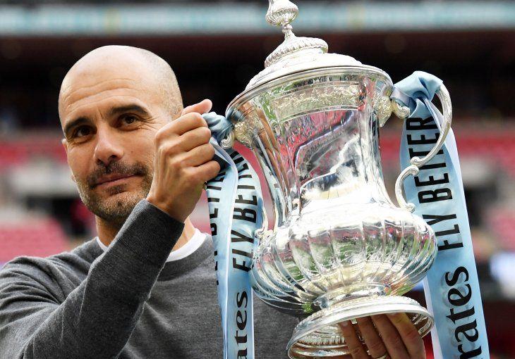 Pep Guardiola levanta el trofeo conseguido en la temporada.