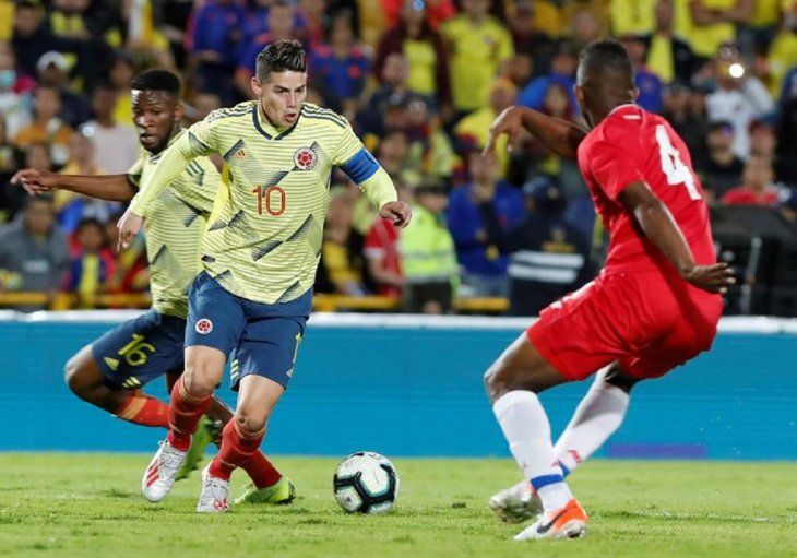 El jugador James Rodríguez (c) deColombiadisputa el balón con Fidel Escobar.