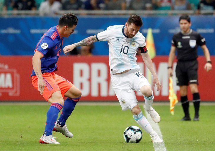 CAPITANES. James Rodríguez y Lionel Messi disputan un balón.