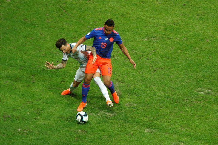 Luis Muriel disputando el balón con Renzo Saravia de Argentina.