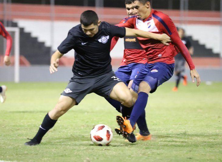 Jugadores de Nacional y Libertad disputan el balón durante un amistoso.