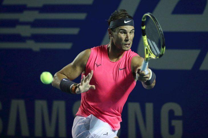 Rafael Nadal devuelve una pelota durante un partido de tenis.