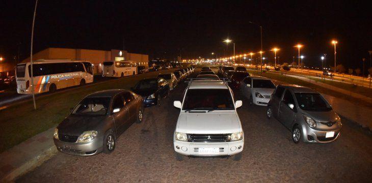 En la Costanera de Asunción se ven varias filas de vehículos en la noche del domingo para que sus ocupantes puedan vacunarse este lunes. Foto de Dardo Ramirez.