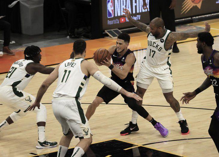 El escolta de los Phoenix Suns Devin Booker (2-R) en acción entre Milwaukee Bucks (L-R) Jrue Holiday