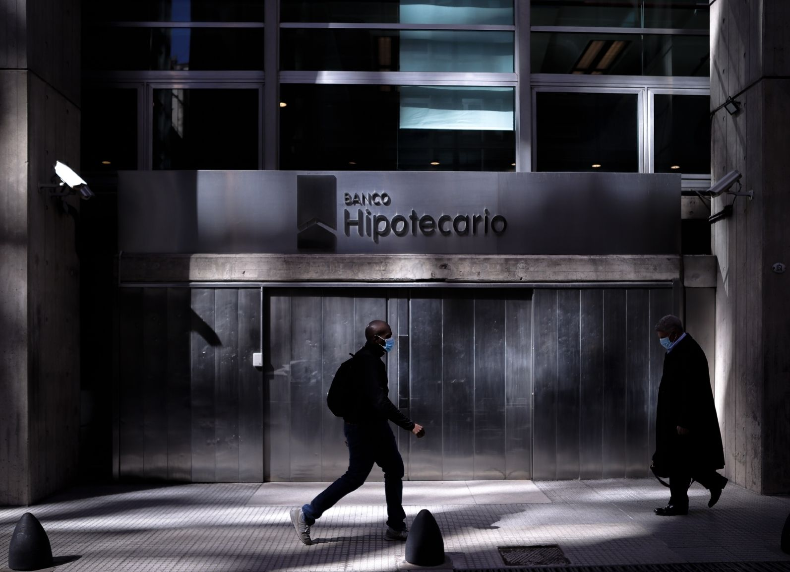 Ahorro. Transeúntes caminan frente a un banco en Buenos Aires. La desconfianza lleva a los argentinos a guardar su dinero fuera del sistema financiero tradicional.