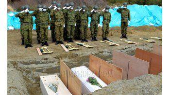 Miembros de las Fuerzas de autodefensa japonesas montan guardia junto a los ataúdes con víctimas del terremoto y posterior tsunami que sacudió la ciudad de Higashi Matsushima, prefectura de Miyagi (Japón). EFE