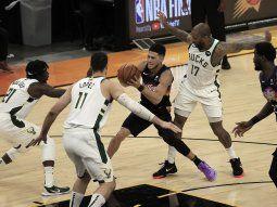 El escolta de los Phoenix Suns Devin Booker (2-R) en acción entre Milwaukee Bucks (L-R) Jrue Holiday, Brook Lop y P.J. Tucker en la segunda mitad del segundo partido de la serie de playoffs de las Finales de la NBA 2021 entre Milwaukee Bucks y Phoenix Suns el en Phoenix Suns Arena en Phoenix.