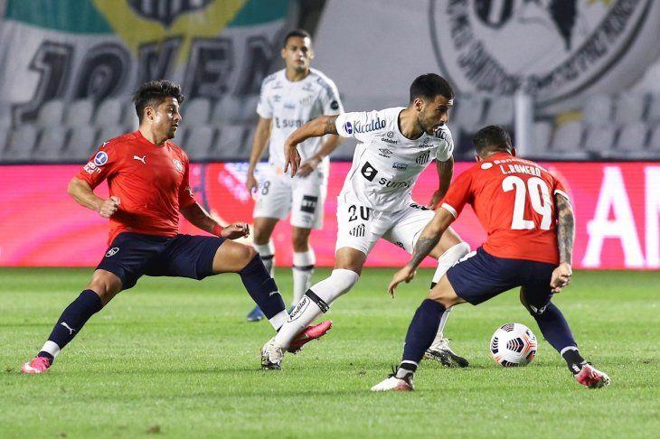 Jugadores de Santos e Independiente se disputan el balón.