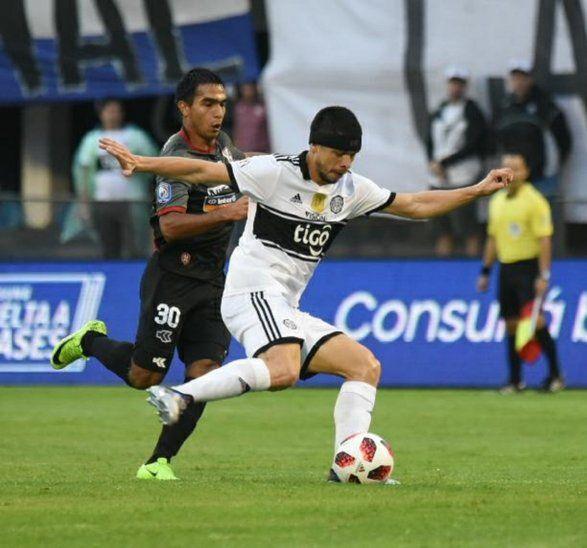 Rodrigo Rojas golpea el balón ante el acoso de un jugador de River.
